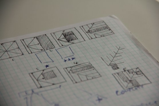 A photograph showing gridded paper with pen sketches on it showing diagonal movement of lines