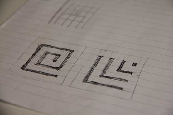A page taken from a ledger showing crude pen drawings of a geometric grid with a snail-like shape filled in one, and radiating right angles in another.